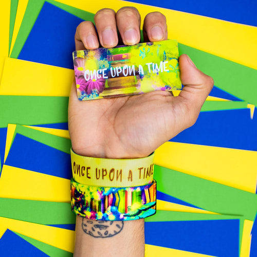 Studio Image of hand holding card that says Once Upon A Time with 2 Once Upon A Time straps on their wrist in front of a colorful background