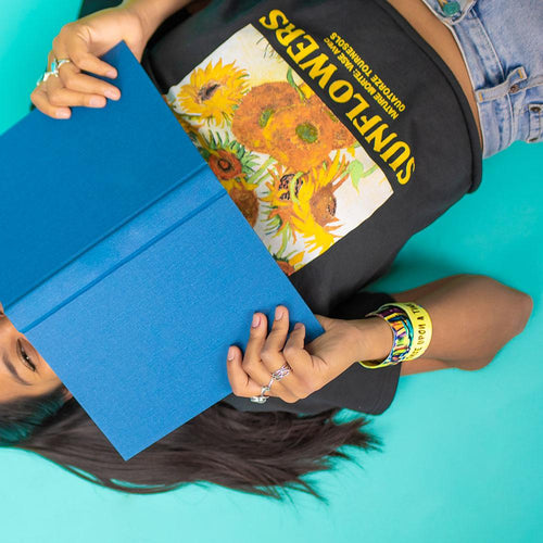 Studio image of model laying down with a blue book covering their face and 2 Once Upon A Time on their wrist