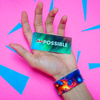 Studio Image of hand holding card that says Possible with a Possible strap on their wrist