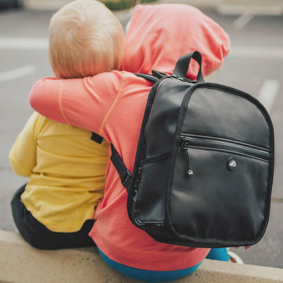 Lifestyle photo of a two little kids. Once is wearing the small black backpack while hugging the smaller little brother in the image