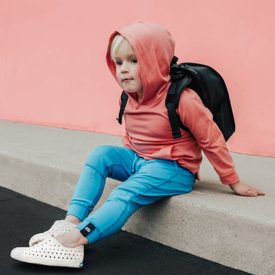 A lifestyle photo of a little boy wearing a pink and blue outfit and sitting on the ground with the small black backpack on his back.