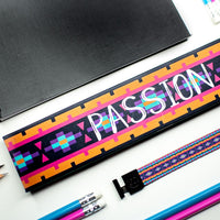 Studio image of Passion and it's box on a desk next to pencils and a folder
