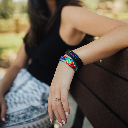 Lifestyle photo up close of a girl's wrist resting on a bench showing the inside and outside design of the peace single
