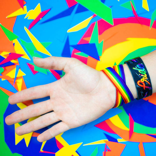 Studio image close up of Pride and a double wristband called Love Wins on someone's wrist in front of a colorful background