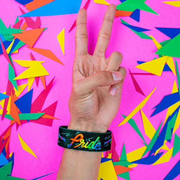 Studio close up image of a hand giving the peace hand sign in front of a colorful background and wearing a Pride strap