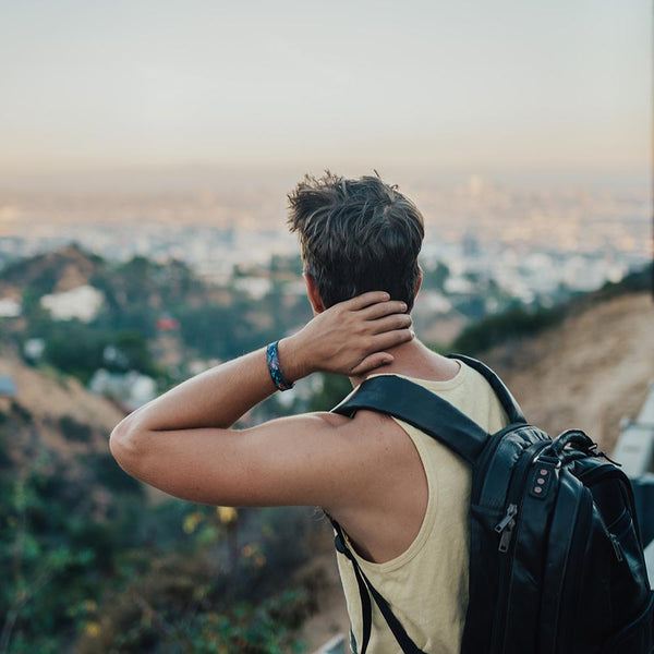 Lifestyle image of someone wearing a backpack over looking a cityscape with Prove Them Wrong on their wrist