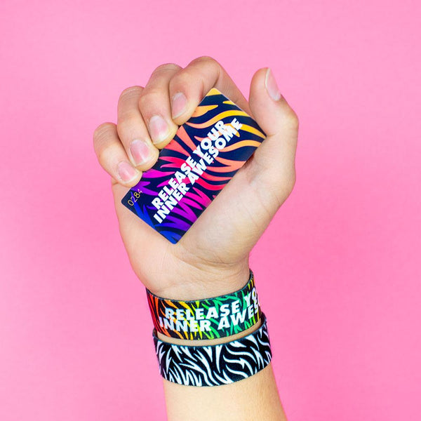 Studio Image of hand holding card that says Release Your Inner Awesome with 2 Release Your Inner Awesome straps on their wrist