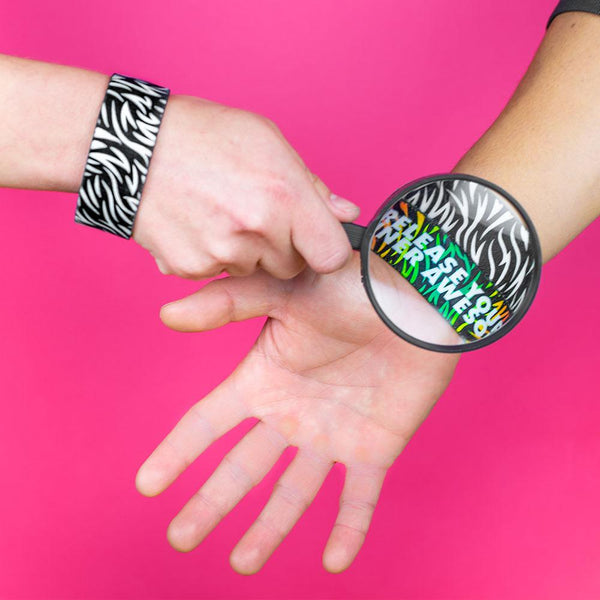Studio image of a hand, wearing a Release Your Inner Awesome and holding a magnified glass over 2 Release Your Inner Awesome on someone else's wrist