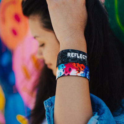 Young adult woman wearing two reflect ZOX with hand close to head. One ZOX shows the inside while the other shows the outside