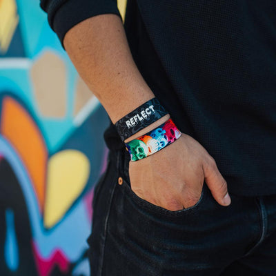 Young adult male wearing two reflect ZOX with hand in his pocket. One ZOX shows the inside while the other shows the outside
