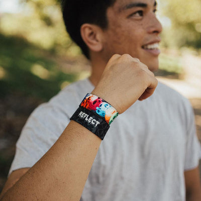 Young adult male wearing two reflect ZOX with hand close to head. The male is smiling. One ZOX shows the inside while the other shows the outside
