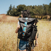 Lifestyle photo of someone hiking with a backpack on while the roll capsule is connected to the side of it