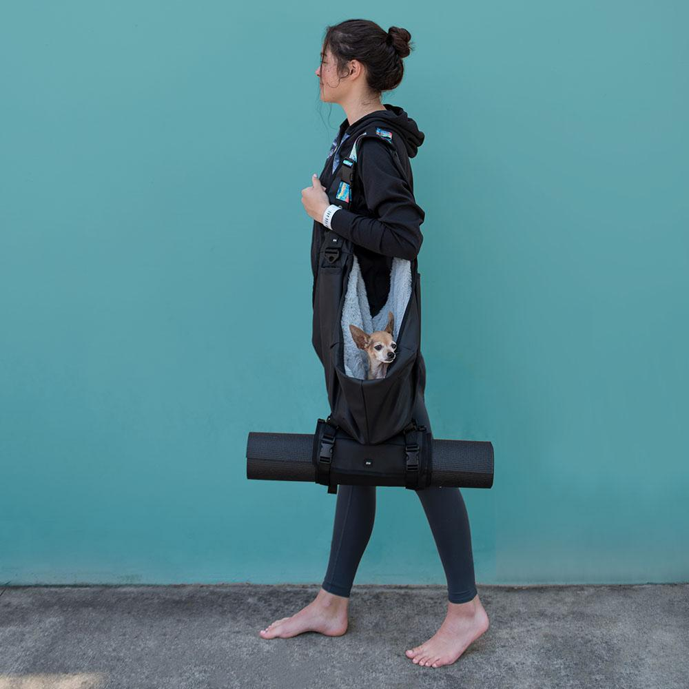 A woman walking with a dog carrier with the roll connected to the bottom that is holding a yoga matt