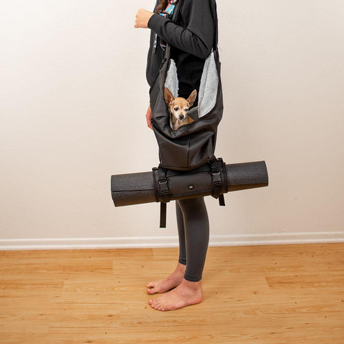 A woman with a dog carrier with the roll connected to the bottom that is holding a yoga matt