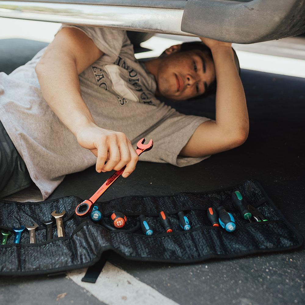 lifestyle image of a man under his car fixing it with the roll open near him full of tools in the pockets
