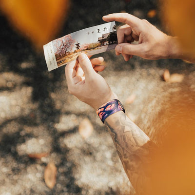 Lifestyle image of hands holding an event ticket with a Spirited Away on their wrist