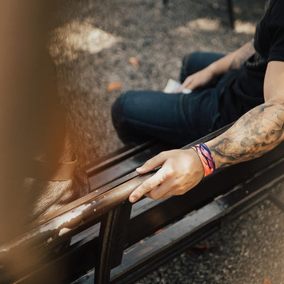 Lifestyle image of arm resting on a bench back with a Spirited Away on wrist