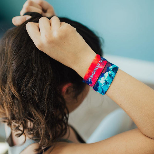 Lifestyle image of someone putting hair in a ponytail and wearing 2 No Shortcut To Success on wrist.