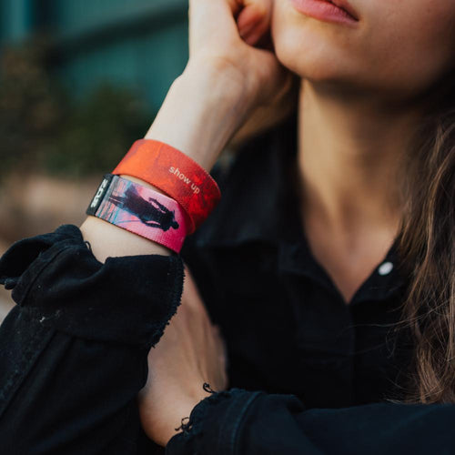 A lifestyle photo of a woman wearing two Show Up wristbands at the same time. One showing the inside and the other showing the outside while her hand is near her jaw