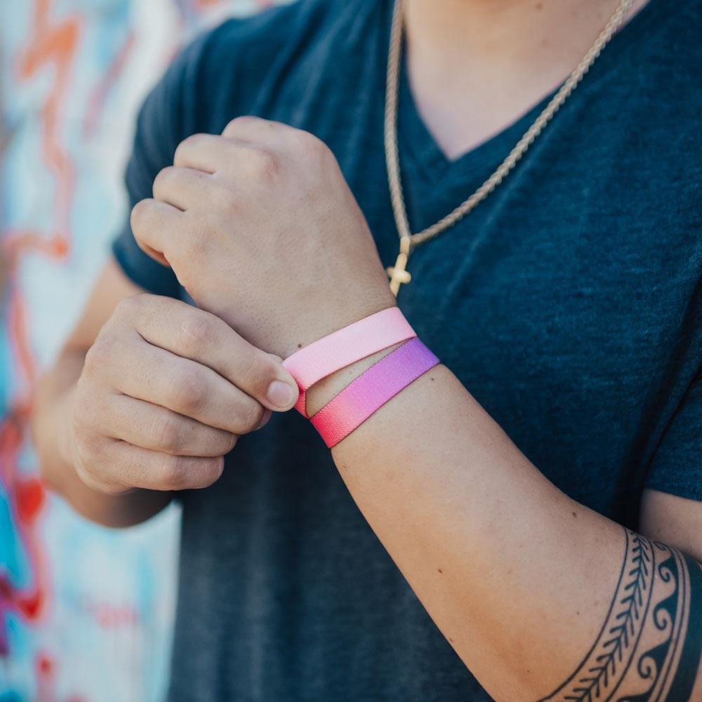 Lifestyle photo of a guy adjusting a no feeling is permanent showing the outside design with a pink to peach gradient above a love yourself single
