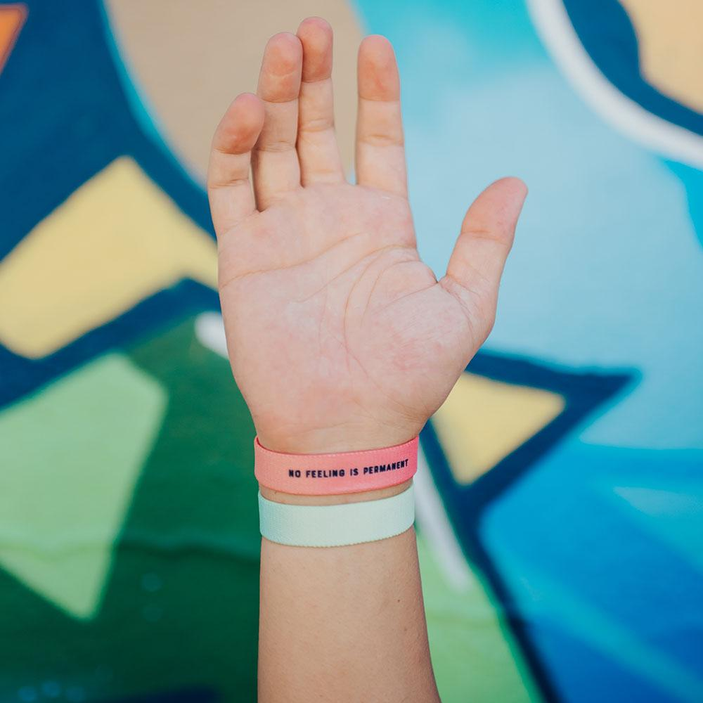 Lifestyle image close up of You Are Perfect For Something and another Zox wristband on model's wrist