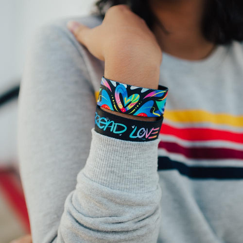 Lifestyle close up image of model's wrist wearing 2 Spread Love straps