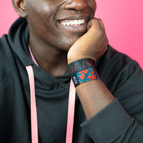 Studio close up image of smiling model and a Self Love on their wrist