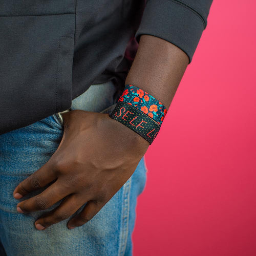 Studio image close up of model's hand in pocket with Self Love on wrist