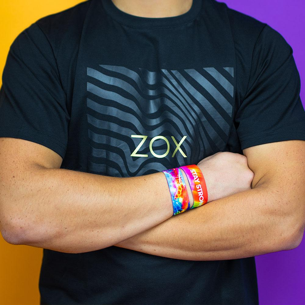 Studio image of model wearing a Zox logo shirt and arms crossed with 2 Stay Strong on wrist