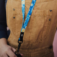 Lifestyle close up image of someone wearing the Starry Night lanyard and holding it by the clip