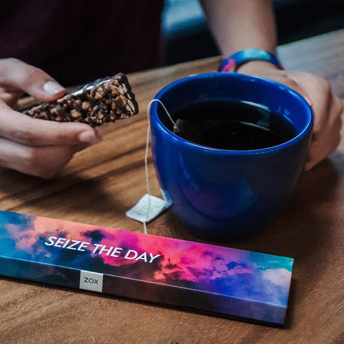 Lifestyle close up image of someone having tea and a biscuit wearing Seize The Day with it's box on the table next to the cup