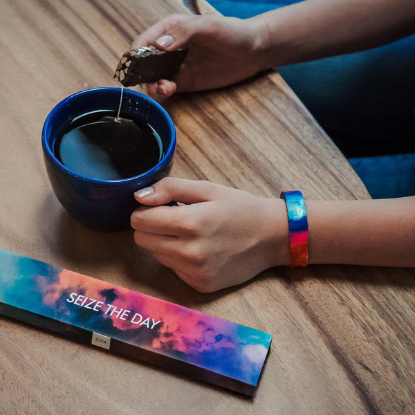 Lifestyle image of someone having coffee and a biscuit wearing Seize The Day with it's box on the table next to the coffee