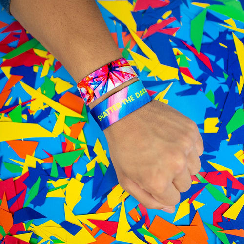 Studio Image of 2 Shatter The Darkness on a wrist in front of a colorful background