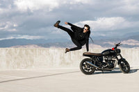 a young male jumping and kicking in the air while next to his motorcycle while wearing a black zipper imperial hoodie
