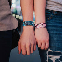 Lifestyle picture of You & Me on models wrists, one blue, one pink.