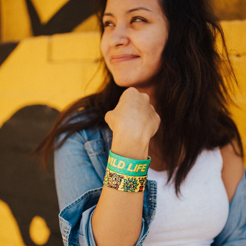 Lifestyle image close up of someone smiling with 2 Wild Life on their wrist