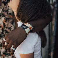 Lifestyle image of someone's arm around someone's shoulder wearing 2 Watch Over Me