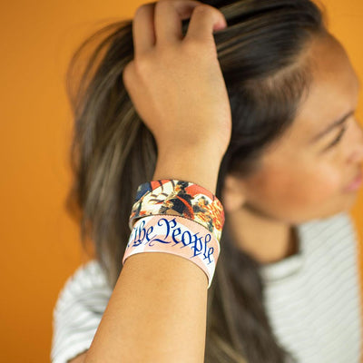 Studio image close up of 2 We The People on model's wrist
