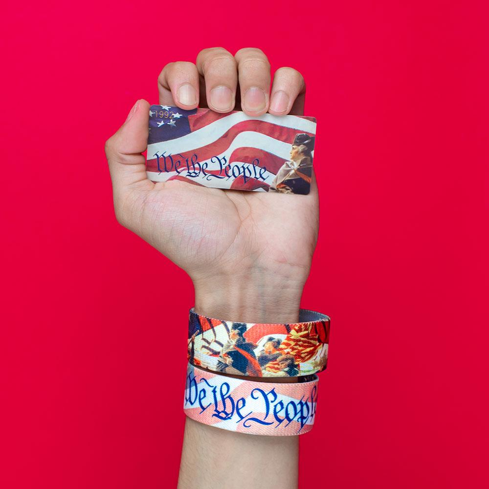 Studio image of hand holding a card that says We The People and wearing 2 We The People on their wrist
