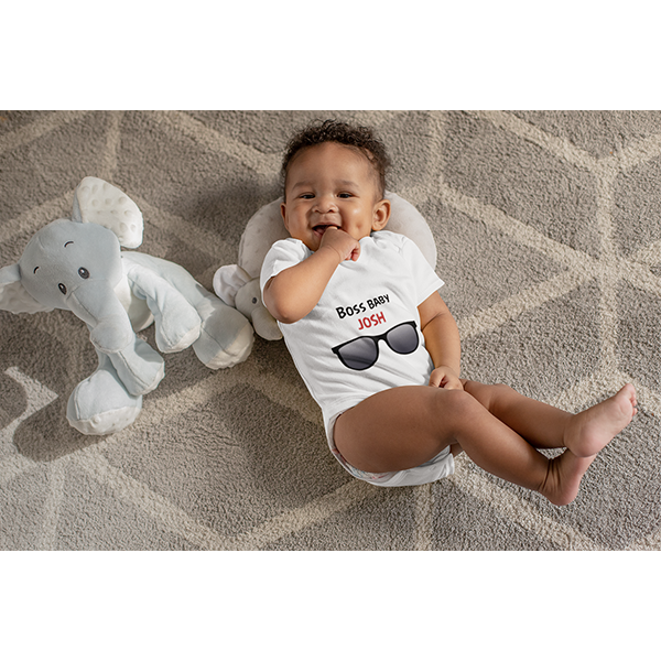 Cute Baby wearing a white Babygrow with the customised design Boss Baby  with the babies name in red writing. Also available in Baby blue and Powder pink.