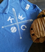 Vintage Kansas City soft style heather blue unisex short sleeve t-shirt featuring the vintage KC logo Sporting the vintage KC logo, crossed baseball bats, Crown and baseball in white print across the chest.  Pictured with a baseball glove - Dalton Ink