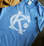 Vintage Kansas City soft style heather blue unisex short sleeve t-shirt featuring the vintage KC logo and a baseball in white print across the chest.  Pictured with a baseball glove - Dalton Ink