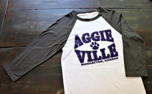 """Aggieville"" from Kansas State University Manhattan, Kansas printed in purple on a white Baseball 3/4 sleeve t-shirt with grey sleeves unisex - Dalton Ink"