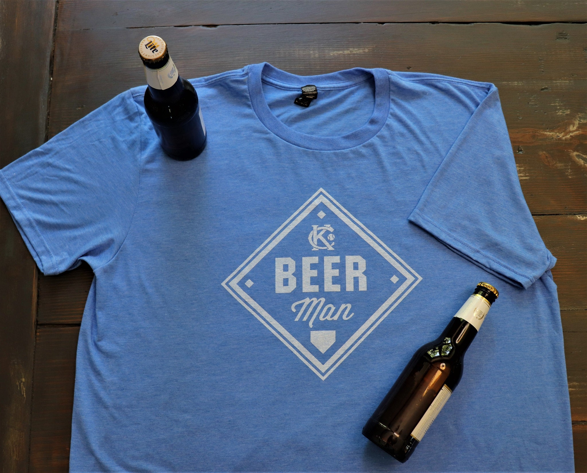 Vintage Kansas City soft style heather blue unisex short sleeve t-shirt featuring the vintage KC logo and a baseball diamond with Beer Man printed in white print across the chest.  Pictured with bottled beers - Dalton Ink