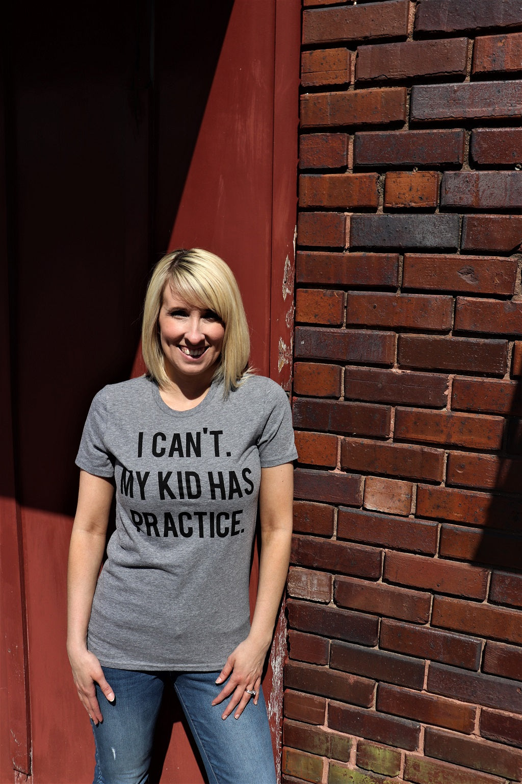 "Women wearing Fun Novelty T-Shirt with saying ""I Can't My Kid Has Practice"" on a Heather Grey short sleeve t-shirt soft style unisex - Dalton Ink"