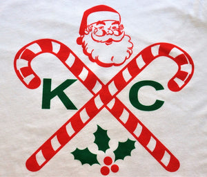 close up of design famed hipster crossed X design modified with two candy canes, KC to represent the Kansas City holiday spirit and featuring our own wonderful throwback Santa reminiscent of the 1950s.  Christmas and holiday clothing from Dalton Ink