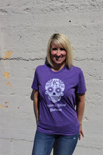 Kansas City West Bottoms Sugar Skull design with vintage KC logo in white print across the chest of a heather purple short sleeve unisex t-shirt - women wearing - Dalton Ink