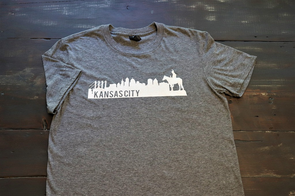 Vintage Kansas City Skyline featuring the historic Scout statue in white print on a charcoal heather grey unisex short sleeve t-shirt - Dalton Ink