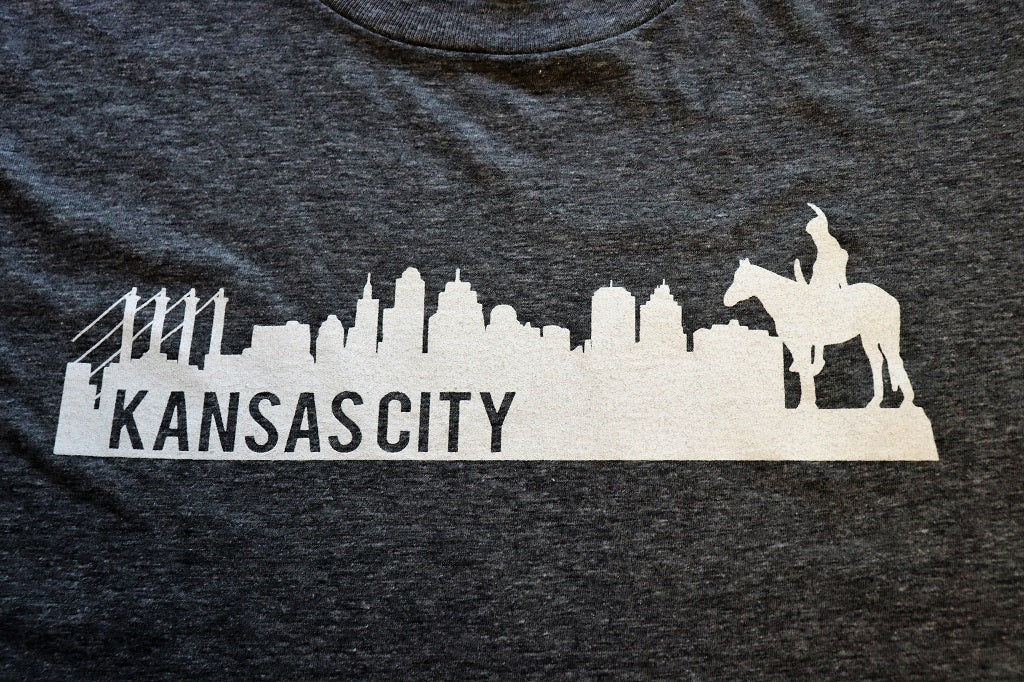 Close Up of Vintage Kansas City Skyline featuring the historic Scout statue in white print on a charcoal heather grey unisex short sleeve t-shirt - Dalton Ink
