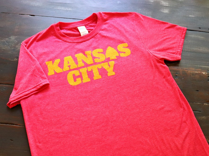 "Heather Red Unisex short sleeve t-shirt featuring Kansas City in gold print on the front and an arrowhead as one of the ""a"" - Dalton Ink"
